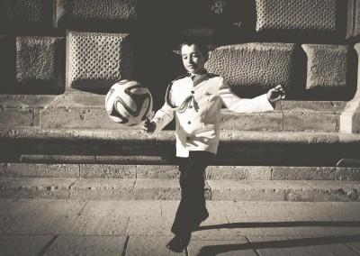 niño de comunión jugando al balón