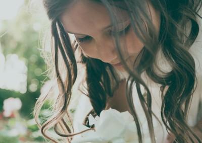 niña de comunión oliendo una flor